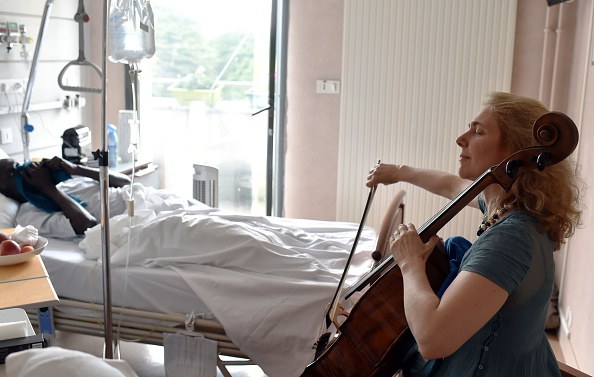 French musician and art therapist Claire Oppert plays music for a patient at an intensive care unit of the Sainte Perine hospital on July 11 in Paris.