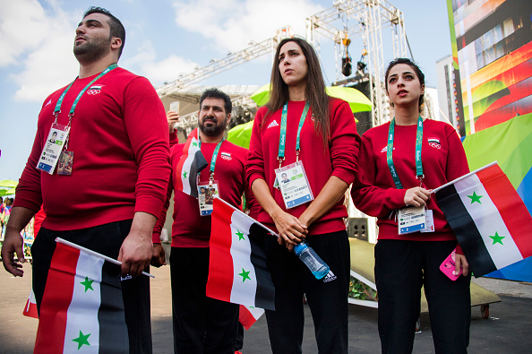 Syrian weightlifter Man Asaad (L), Syrian swimmer Baean Jouma (2nd R) and Syrian Women's Table Tennis Heba Allejji (R) stand for their national anthem during a welcoming ceremony at the Olympic Village ahead of the Rio 2016 Olympic Games in Rio de Janeiro, on August 4.