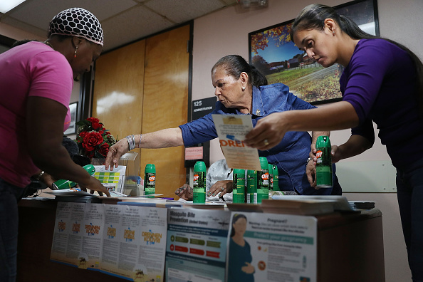 Mira Trujillo (L) picks up bug repellent from Brunilda Mendez (C) and Rachel Romano who have a table setup to help people prevent getting the Zika virus in a building located in the Wynwood neighborhood where the Zika virus has broken out on August 4 in Miami, Florida.