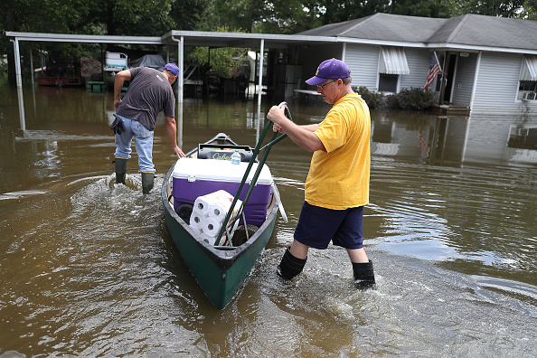 Mike Sittig (L) and Nelson Morgan, Jr. bring supplies to Nelson's father's home to begin the process of cleaning up after flood waters inundated it on August 19 in St. Amant, Louisiana.
