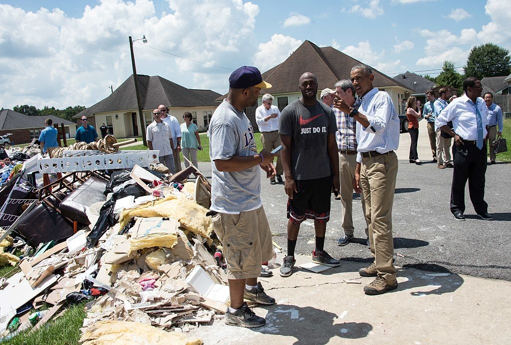 U.S. President Barack Obama speaks with residents as he tours a flood-affected area in Baton Rouge, Louisiana, on August 23.