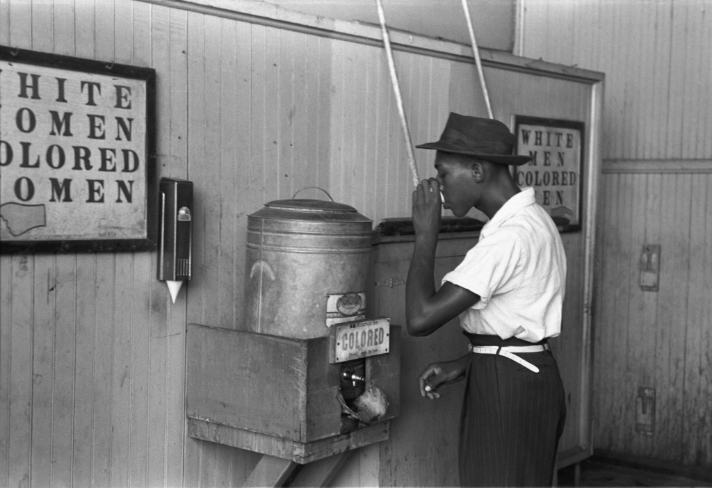 "In Oklahoma City in 1939, a black man drinks from a ""colored"" drinking fountain."