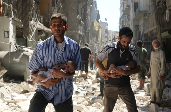 Syrian men carrying babies make their way through the rubble of destroyed buildings following a reported air strike on the rebel-held Salihin neighbourhood of the northern city of Aleppo on September 11.  AFP / AMEER ALHALBI        (Photo credit should read )