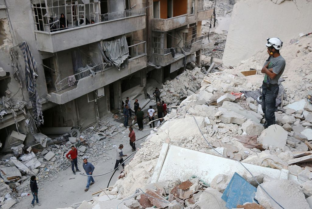 A Syrian civil defense volunteer stands on the rubble of destroyed buildings during a rescue operation following a government forces air strike on the rebel-held neighbourhood of Bustan al-Basha in the northern city of Aleppo, on October 4, 2016.