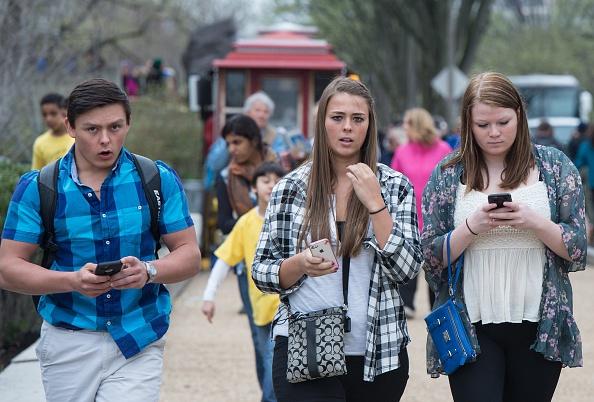Three teens walk with their smartphones in Washington, D.C. on April 8, 2015. A Pew Research Center survey released found that 92 percent of US teens go online daily. The survey of teens between the ages of 13 and 17 found that 73 percent had a smartphone and 30 percent had at least a basic cellphone.