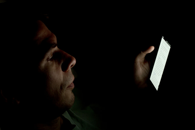A man reads the news on his smart phone.