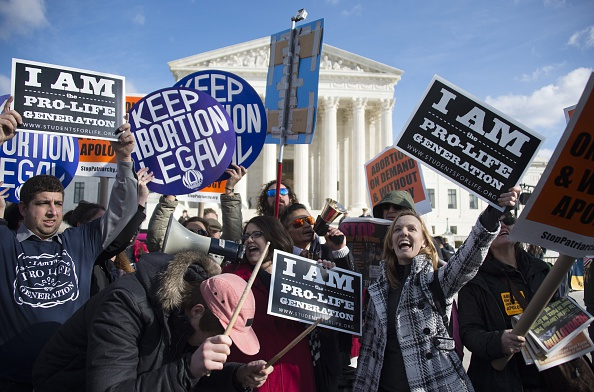 Pro-choice and pro-life activists mingle as they hold up placards and chant in front of the U.S. Supreme Court in Washington, D.C.
