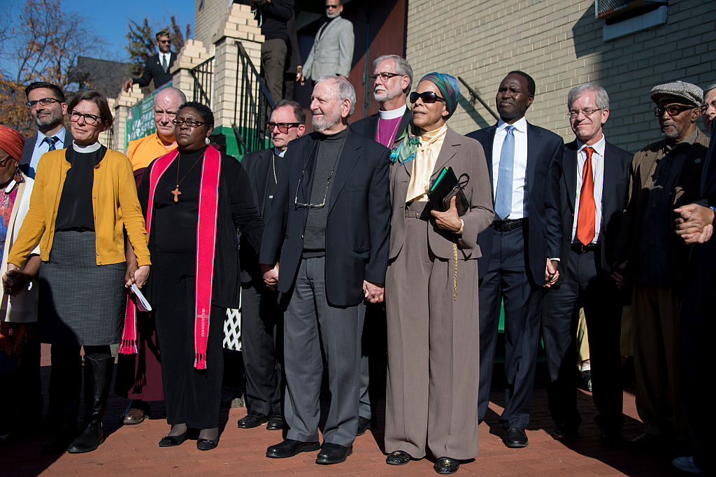 An interfaith coalition of faith leaders stand together holding hands during a press conference on the aftermath of the US presidential election, and rising hate crimes, outside the Masjid Muhammad, The Nation's Mosque, in Washington, DC, November 18, 2016. / AFP / JIM WATSON        (Photo credit should read JIM WATSON/AFP/Getty Images)