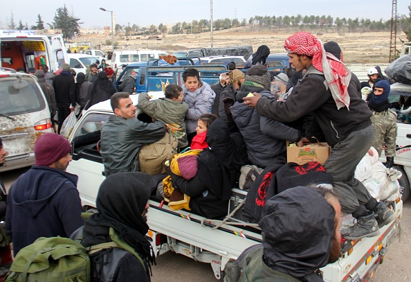 Syrian rebel fighters and civilians who were evacuated from rebel-held neighborhoods in Aleppo arrive in an opposition-controlled region on December 16, 2016.  The Syrian government suspended the evacuation of civilians and fighters from the last rebel-held parts of Aleppo, leaving thousands of people trapped and uncertain of their fate.