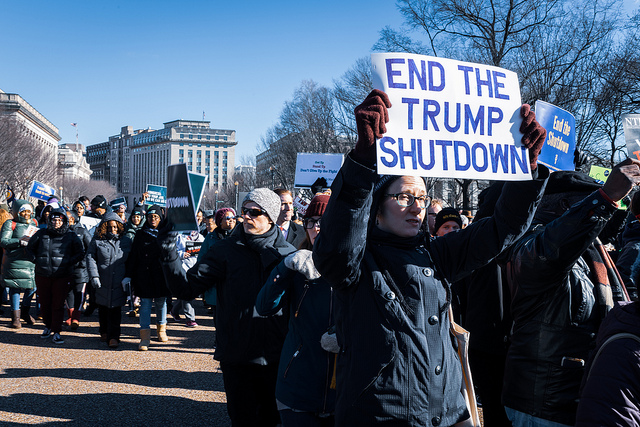 Protesters hold signs demanding an end to the government shutdown.