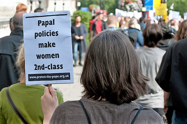 A woman holds a sign at a protest in London.