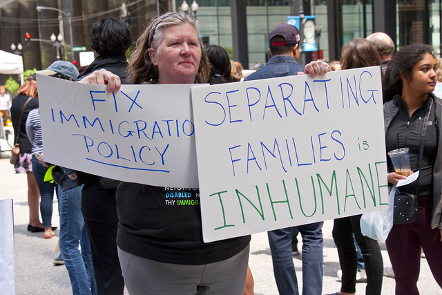 A woman holds signs at a rally in Chicago on June 5, 2018, to protest President Trump's immigration policies.