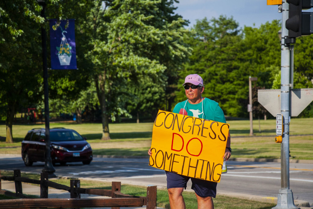 "A man holds a sign asking political leaders in Washington to ""do something"" about gun violence in the wake of the mass shootings in El Paso and Dayton."