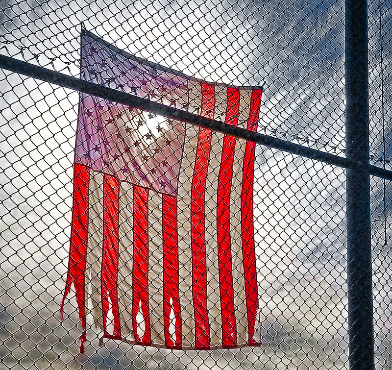 A torn American flag behind a fence on a little league field in California.