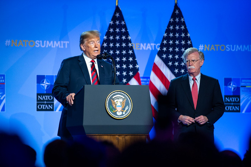 Former national security adviser John Bolton stands beside President Trump at a NATO summit in Brussels in 2018.