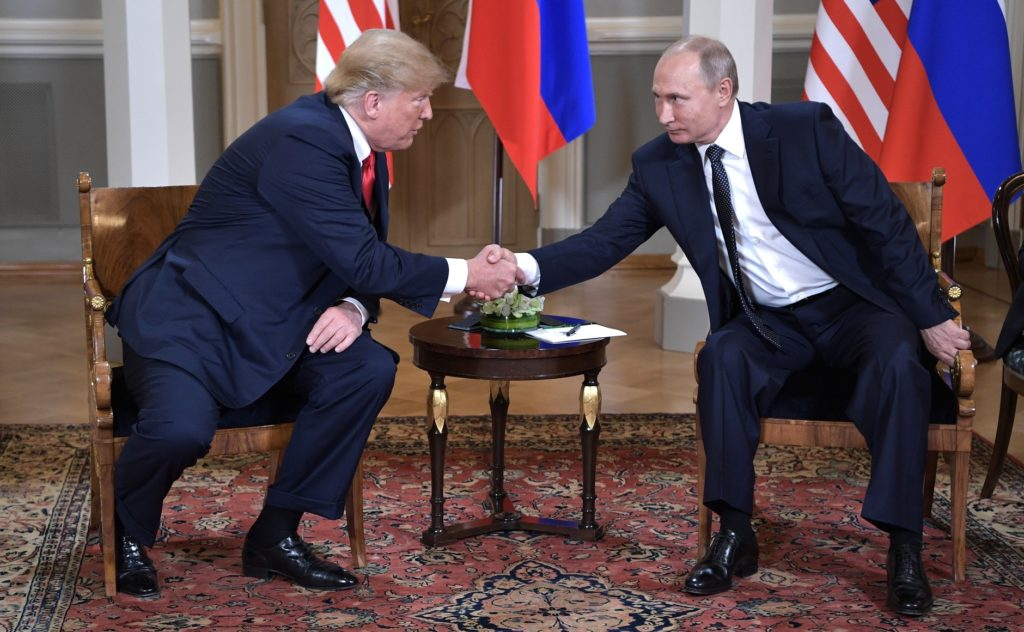 Donald Trump and Vladimir Putin shake hands at a summit in Helsinki in July 2018. A new report by the Senate Intelligence Committee details interactions between Russian government operatives and members of Trump's 2016 campaign staff.