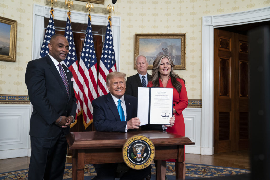 President Trump signs a pardon for ex-convict and Hope for Prisoners CEO Jon Ponder during the Republican national convention. It was one of several events that took place at the White House, raising concerns about violations of the Hatch Act, which prevents the mixing of government functions with partisan political activity.