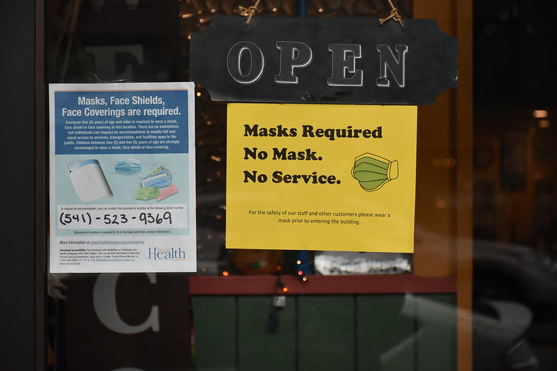 A storefront in Baker City, Oregon displays signs asking customers to follow Covid-19 public health guidance.