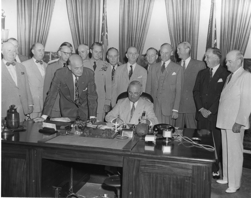 President Harry S. Truman is seated at his desk in the Oval Office, signing the National Security Act Amendments of 1949, which converted the National Military Establishment into a new Department of Defense and made other changes in the national security system.