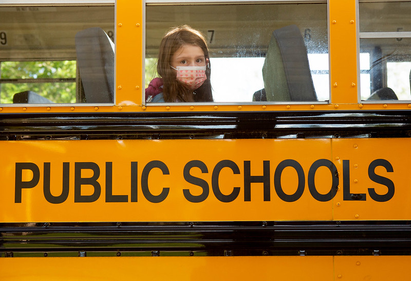 An elementary student waits for her bus to leave school after dismissal.