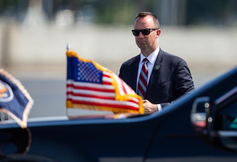 A U.S. Secret Service agent accompanies a presidential motorcade.