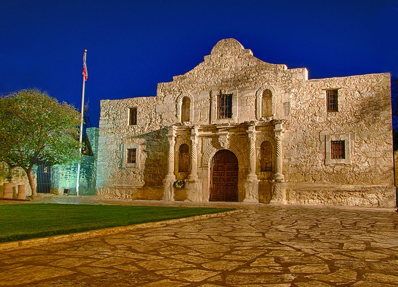 A picture of the Alamo at night with the Texas flag waving to the side.