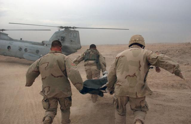 US Army Soldiers rush a wounded soldier to a waiting US Marine Corps helicopter during an operation in Fallujah, Iraq, during Operation IRAQI FREEDOM.