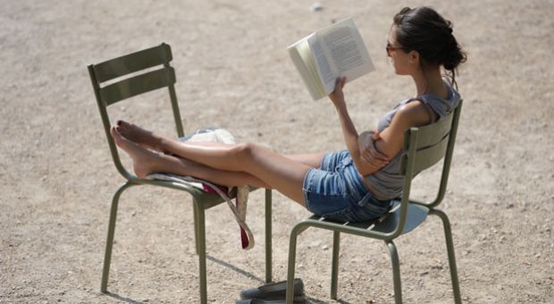 A women reads a book under the sun in the Luxembourg gardens in Paris, on July 1, 2010.