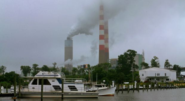 A boat stands in the shadow of the coal-fired Morgantown Generating Station, on May 29, 2014 in Newburg, Maryland.