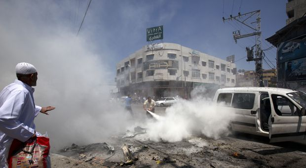 A man uses a fire extinguisher after a vehicle was targeted in an Israeli airstrike on Gaza City on July 8, 2014. An Israeli air strike on a car in Gaza City killed four people, medics said, taking the death toll for the day to five from Israel's air campaign.
