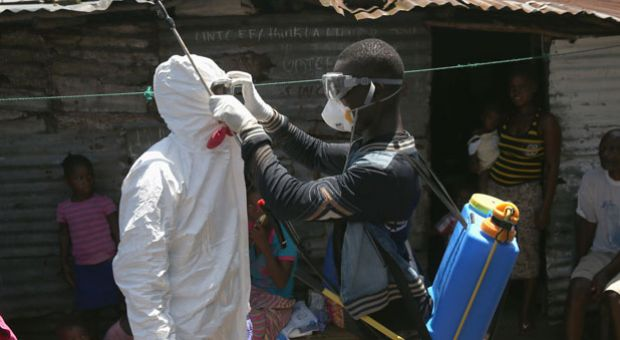 Health workers suit up in protective clothing (PPE), before taking people suspected of having Ebola to a re-opened Ebola holding center in the West Point neighborhood on October 17, 2014 in Monrovia, Liberia. The World Health Organization says that more than 4,500 people have died due to the Ebola epidemic in West Africa with a 70 percent mortality rate for those infected with the virus.