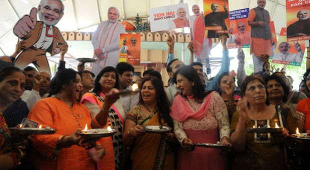 Indian supporters of chief minister of western Gujarat state and main opposition Bharatiya Janata Party (BJP) prime ministerial candidate Narendra Modi sing a prayer hymn during a ritual for Modi's victory at a temple in Ahmedabad on May 15, 2014. India's triumphant right-wing opposition said it was headed for a decisive majority in the world's biggest election after exit polls showed its hardline leader Narendra Modi closing in on victory.