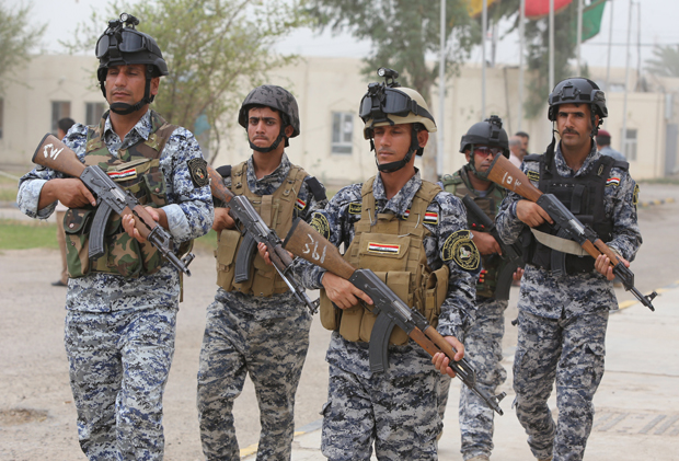 Iraqi policemen are seen inside a military base in the capital Baghdad, on June 11, 2014, after the parliament had received a joint request from Iraqi Prime Minister Nuri al-Maliki and the president's office to declare a state of emergency. Jihadists seized in the city of Mosul, Iraq's second and Nineveh province on June 10, in a major blow to the government apparently unable to halt the progress of armed.
