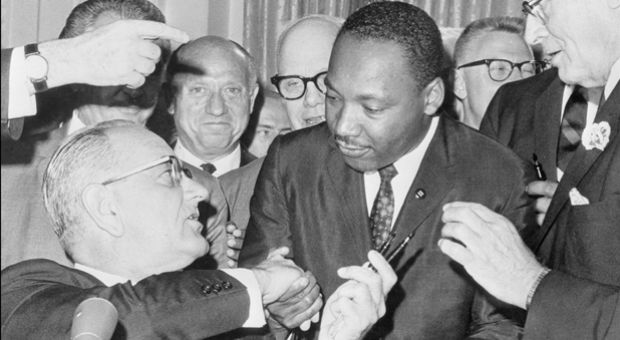 US President Lyndon Johnson (l) shakes hands with the US clergyman and civil rights leader Martin Luther KIng (c) on July 3, 1964 in Washington DC, after handing him a pen during the ceremonies for the signing of the civil rights bill at the White House.