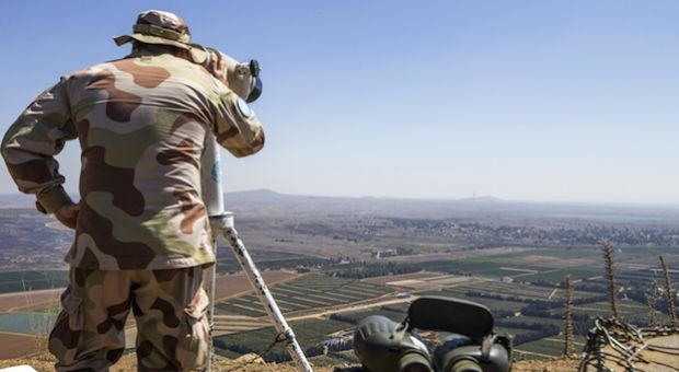A European member of United Nations Disengagement Observer Force (UNDOF) uses binoculars to watch the Syrian side of the Golan Heights as he stands in the Israeli-occupied Golan Heights on September 5, 2014. Israel is closely monitoring the fighting between Syrian troops and Islamist rebels close to the armistice line on the Golan out of fear of a spillover of the internal conflict.