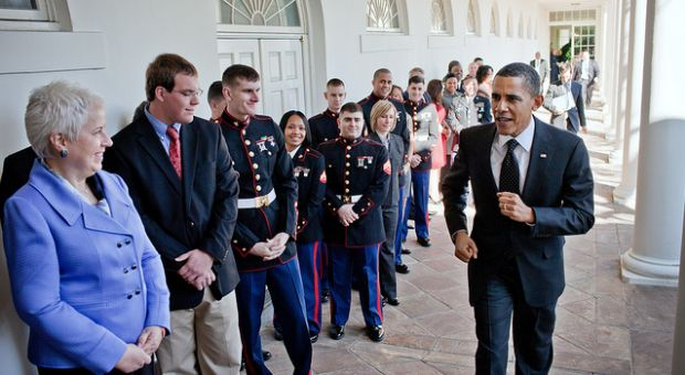 President Barack Obama passes staff from the White House Military Office as he jogs along the Colonnade of the White House following an event that ran late, March 1, 2011. The military personnel and their families were lined up to take departure pictures with the President in the Oval Office.