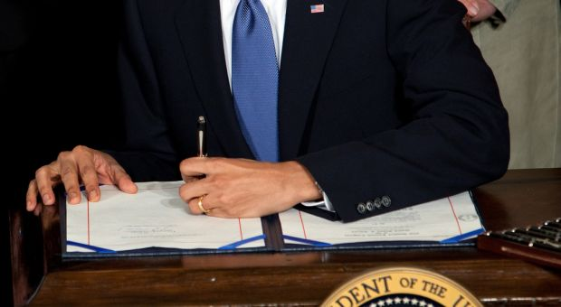 President Barack Obama signs the health insurance reform bill in the East Room of the White House, March 23, 2010.