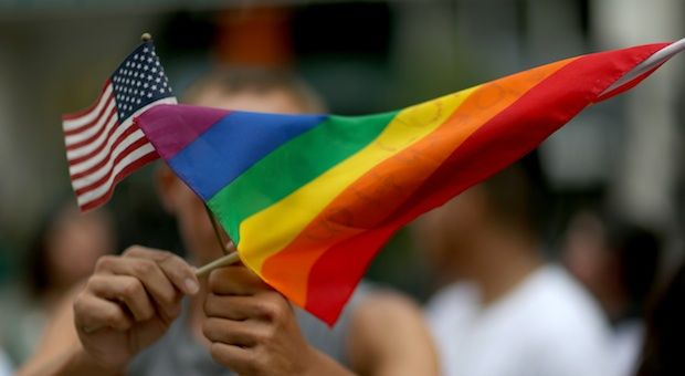 A protester holds an American flag and rainbow flag in front of the Miami-Dade Courthouse to show his support of the LGBTQ couples inside the courthouse were asking the state of Florida to recognize their marriage on July 2, 2014 in Miami, Florida.